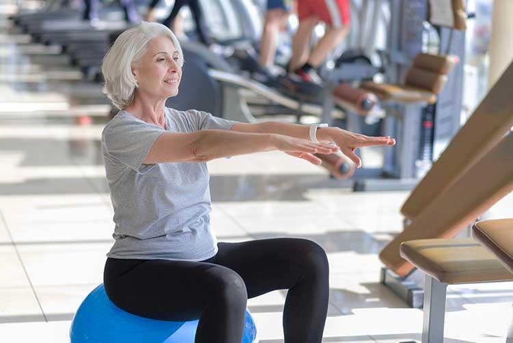 Ältere Dame macht Beckenbodenübungen auf einem Gymnastikball. ACTICORE hilft beim BBT.
