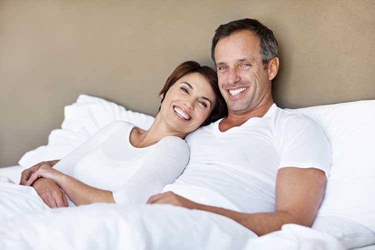 Ein glückliches Pärchen im Bett. Mit ACTICORE wird die Sexualität wieder angeregt und aktiver