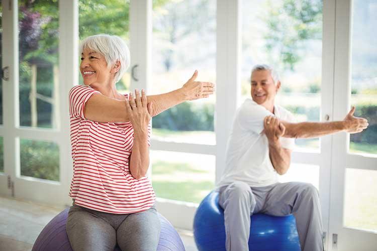 Älteres Pärchen auf Gymnastikbällen im Training. Beckenbodentraining unterstützt durch ACTICORE