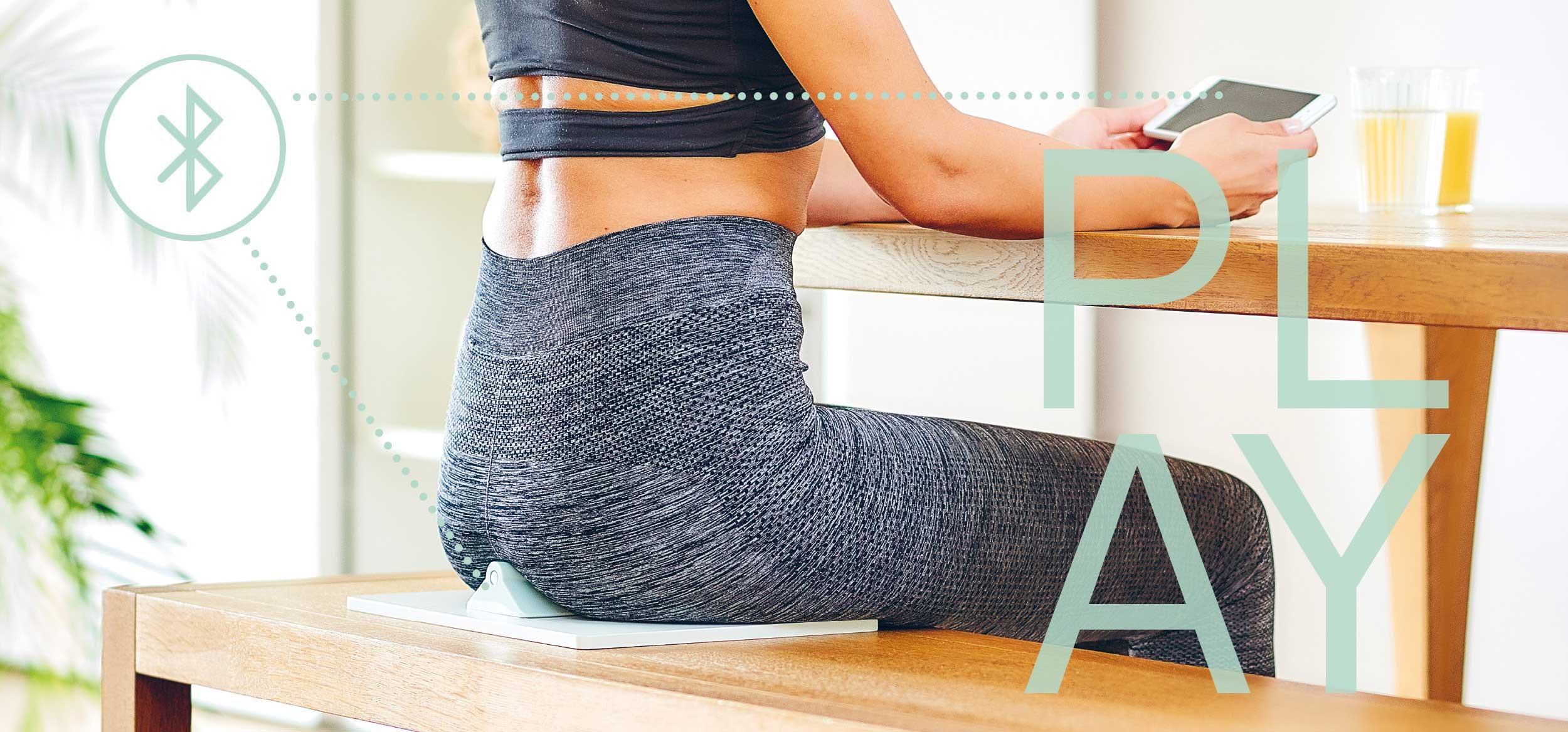 Sportliche Frau benutzt den ACTICORESensor Seat und spielt mit derApp von ACTICORE