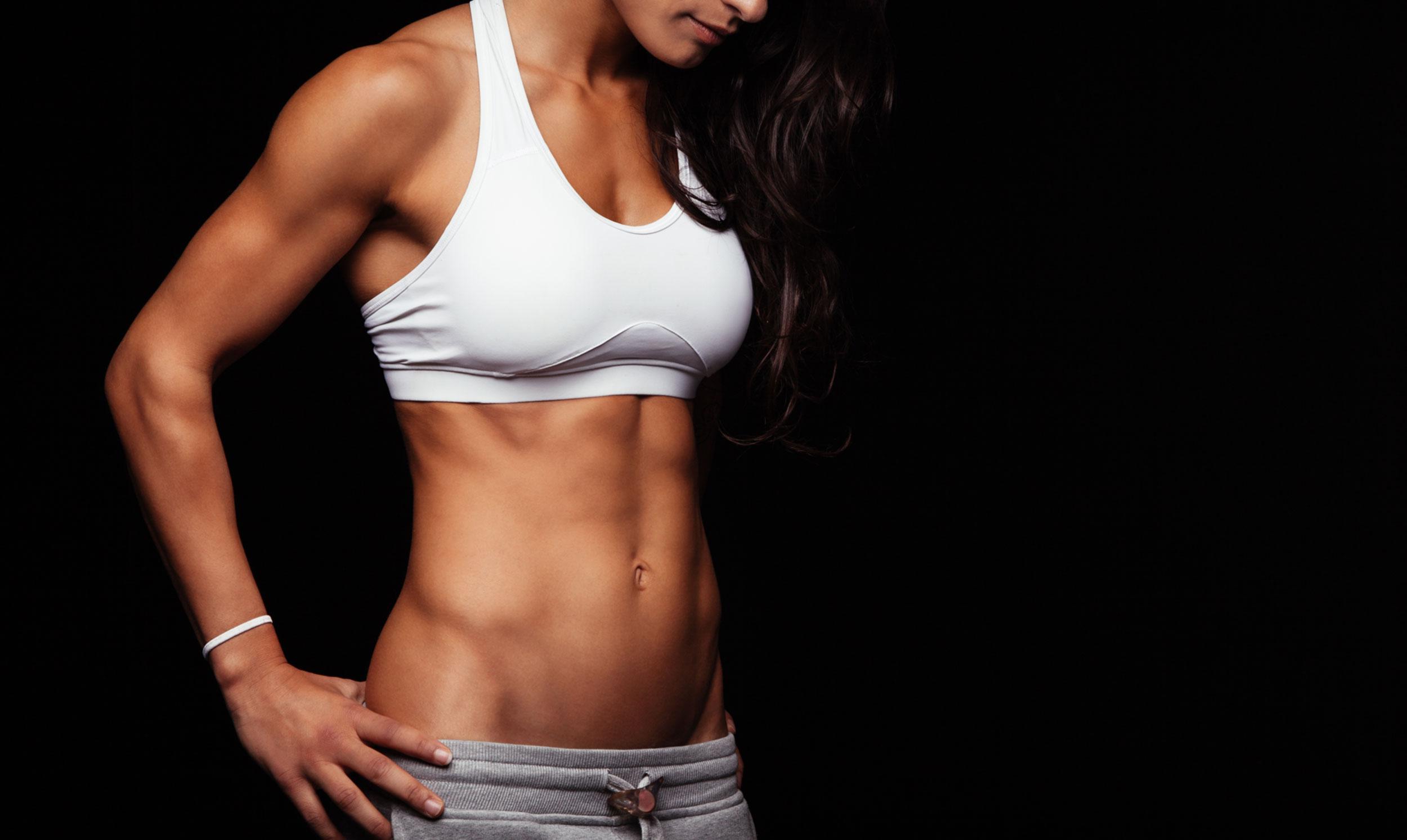 Sportliche Frau mit sichtbarer Bauchmuskulatur. ACTICORE hilft beim Training.